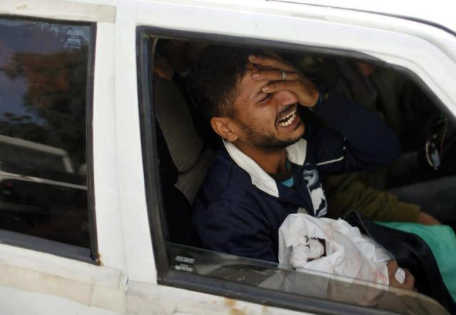 The father of Palestinian baby girl Hanen Tafish, who according to hospital officials was killed in an Israeli air strike, carries her body as he sits in a car during her funeral in the northern Gaza Strip November 16, 2012.
