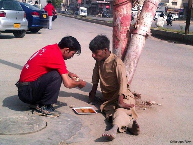 A waiter at a restaurant buys food and feeds a disabled homeless man with his own hands in Karachi, Pakistan.