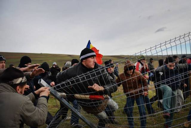 Romanian protesters tear down the fence of the exploring perimeter of US energy giant Chevron in Pungesti, Romania on December 7, 2013.